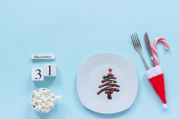 Calendario 31 dicembre. albero di natale di cioccolato dolce sul piatto, posate, tazza di cacao