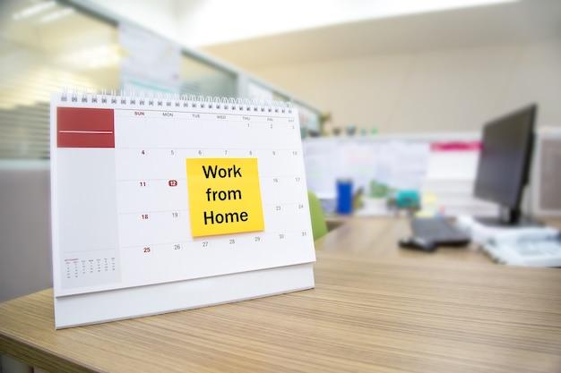 Calendario sulla scrivania con lavoro di nota cartacea da casa.