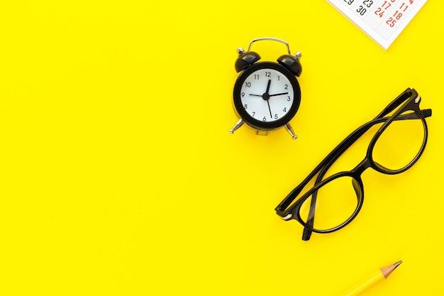 Calendario, occhiali da vista e sveglia su sfondo giallo. scadenza, pianificazione per riunioni di lavoro o concetto di pianificazione del viaggio. vista piana laico e superiore con lo spazio della copia.