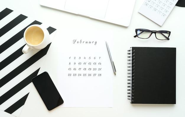 Calendario di febbraio su ley piatto desktop bianco con una tazza di caffè e un taccuino