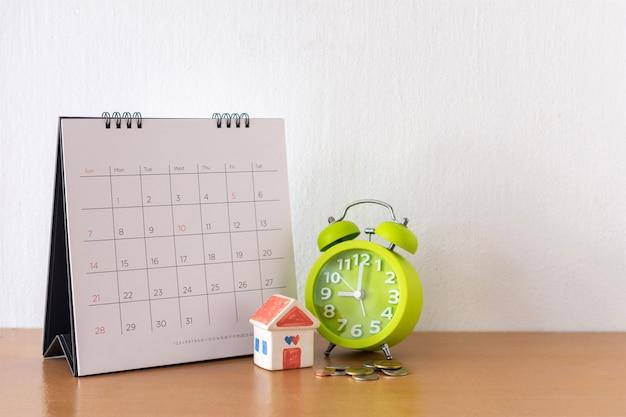 Calendario e casa sul tavolo. giorno di acquisto o vendita di una casa o pagamento per affitto o prestito.