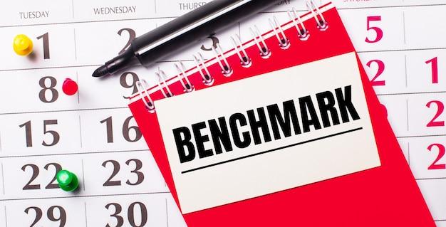 Sul calendario c'è una carta bianca con il testo benchmark. nelle vicinanze c'è un blocco note rosso e un pennarello. vista dall'alto