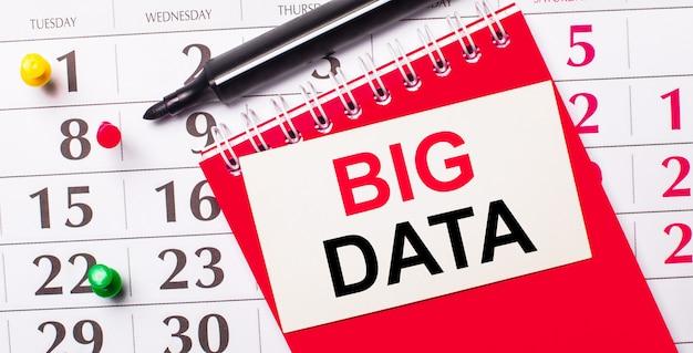 Sul calendario c'è una carta bianca con il testo big data. nelle vicinanze c'è un blocco note rosso e un pennarello. vista dall'alto