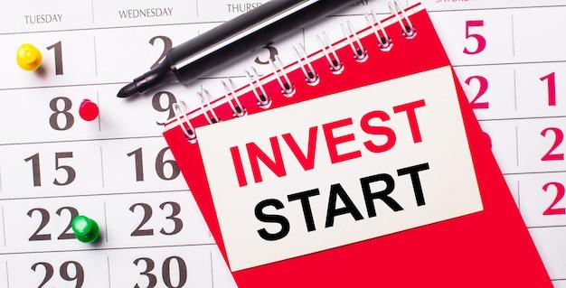 Sul calendario c'è una carta bianca con il testo invest start. nelle vicinanze c'è un blocco note rosso e un pennarello. vista dall'alto