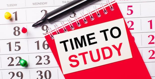Sul calendario c'è un cartoncino bianco con il testo time to study. nelle vicinanze c'è un blocco note rosso e un pennarello. vista dall'alto