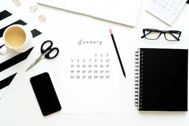 Calendario di gennaio su ley piatto desktop bianco con una tazza di caffè e un'area di lavoro per notebook