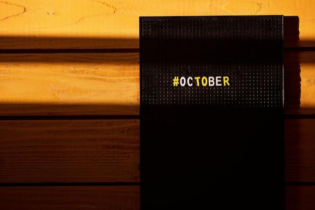 Mese di calendario ottobre con hashtag realizzato su una bacheca retrò su uno sfondo giallo in legno, con linee solari