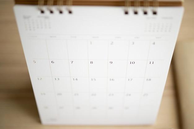 Pagina del calendario si chiuda sul concetto di riunione di appuntamento di pianificazione aziendale del fondo della tavola di legno