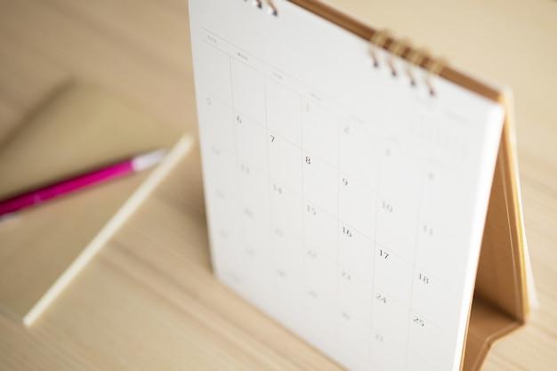La pagina del calendario si chiuda sul fondo di legno della tavola con il concetto di riunione di appuntamento di pianificazione aziendale del taccuino e della penna
