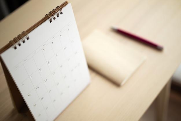 La pagina del calendario si chiude sullo sfondo del tavolo in legno con il concetto di riunione dell'appuntamento per la pianificazione aziendale di penna e taccuino