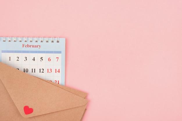 Pagina del calendario e busta con una lettera d'amore su uno sfondo rosa. concetto di san valentino. copia spazio.