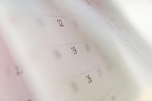 Foglio di sfogliamento della pagina del calendario da vicino sullo sfondo del tavolo dell'ufficio pianificazione degli appuntamenti di pianificazione degli appuntamenti concetto di riunione