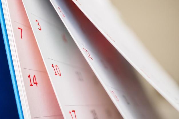 Foglio capovolgimento della pagina del calendario da vicino sulla pianificazione del programma di affari del fondo della tavola dell'ufficio