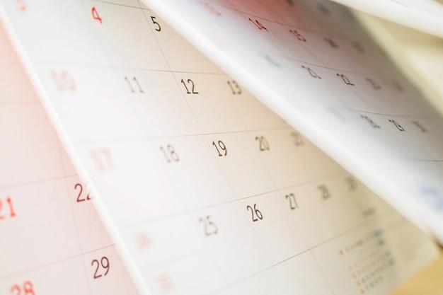 Foglio capovolgimento della pagina del calendario si chiuda sul concetto di riunione di appuntamento di pianificazione del programma di affari della tabella dell'ufficio
