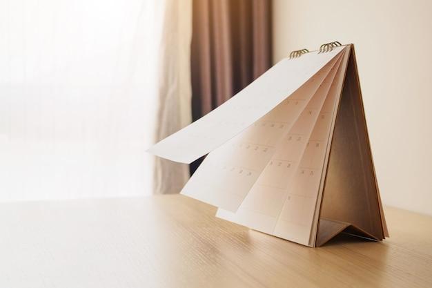 Foglio capovolgimento della pagina del calendario sul concetto di riunione di appuntamento di pianificazione di pianificazione di affari del fondo della tavola di legno