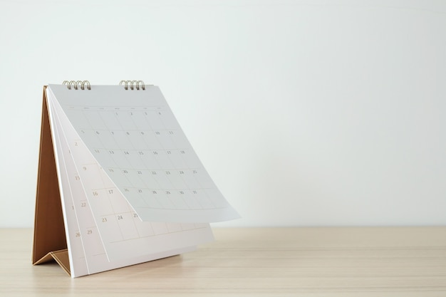 Foglio di capovolgimento della pagina del calendario sul concetto di riunione di appuntamento di pianificazione del programma di affari del fondo della tavola di legno