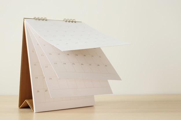 Foglio capovolgimento della pagina del calendario sul concetto di riunione di appuntamento di pianificazione del programma di affari del fondo della tavola di legno