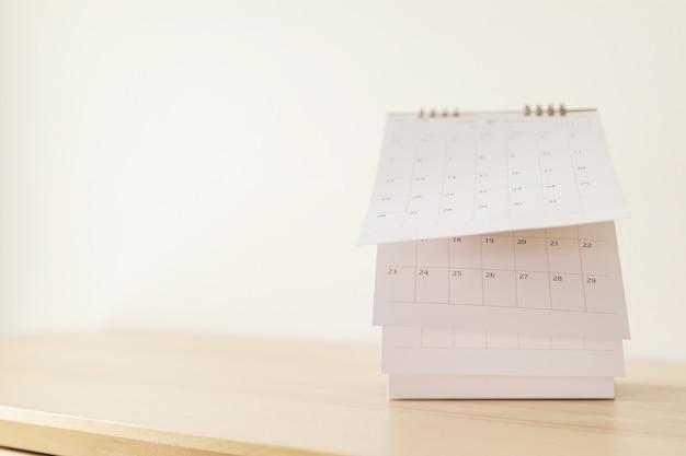 Foglio di lancio della pagina del calendario sul concetto di riunione di appuntamento di pianificazione di appuntamento di pianificazione di legno del fondo della tavola