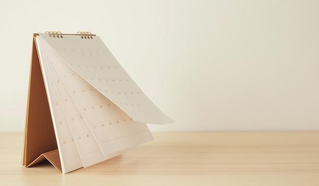 Foglio capovolgimento della pagina del calendario sulla pianificazione di pianificazione aziendale del fondo della tavola di legno