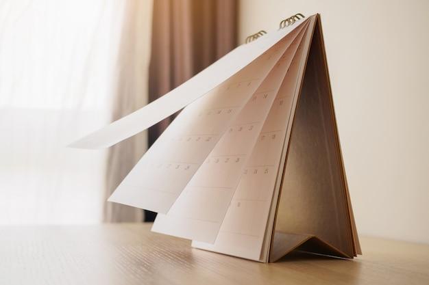 Pagina del calendario lanciando foglio sulla tavola di legno. concetto di riunione appuntamento pianificazione pianificazione aziendale