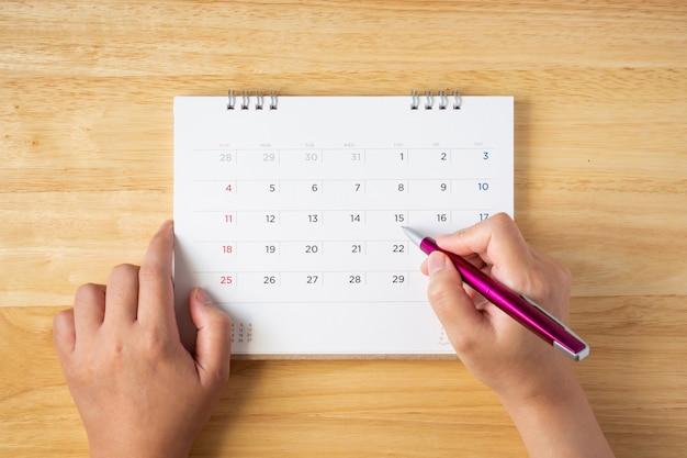 Pagina del calendario sul tavolo con mano femminile che tiene la penna, vista dall'alto