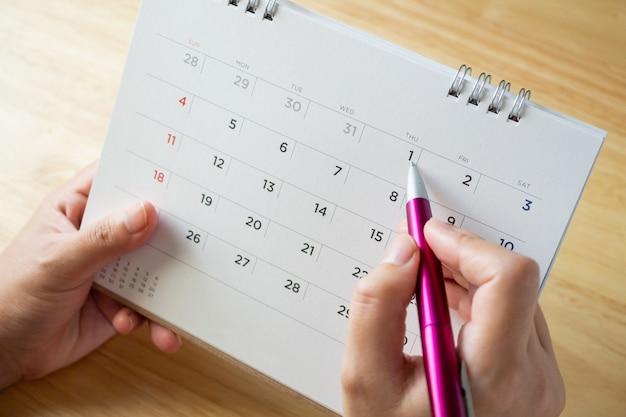 Pagina del calendario con mano femminile che tiene la penna sul tavolo della scrivania