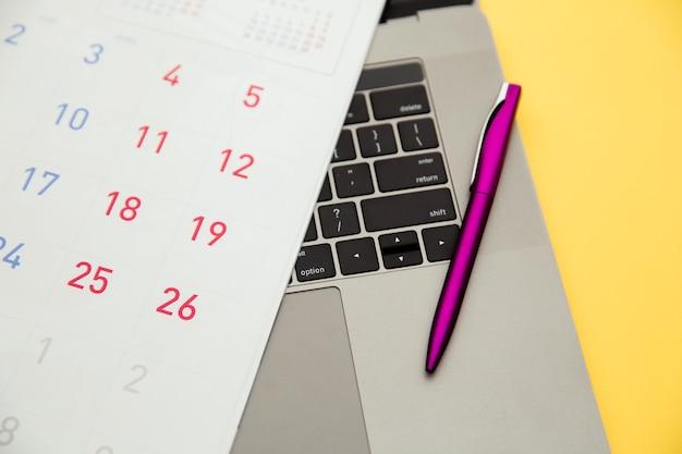 Calendario e penna sulla tastiera.