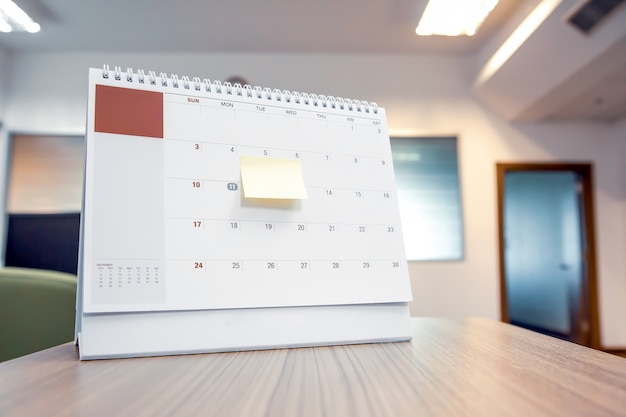 Calendario con nota di carta sulla scrivania per pianificatore di eventi.