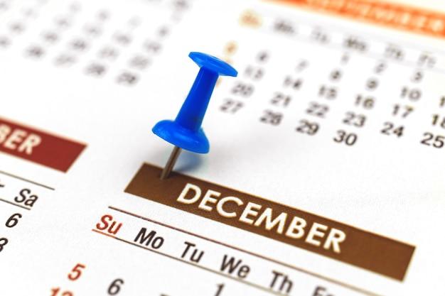 Calendario con puntina da disegno, primo piano del mese di dicembre, concetto di pianificatore, foto di messa a fuoco selettiva