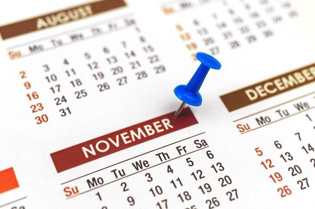 Calendario con puntina da disegno, primo piano del mese di novembre, concetto di pianificatore, foto di messa a fuoco selettiva