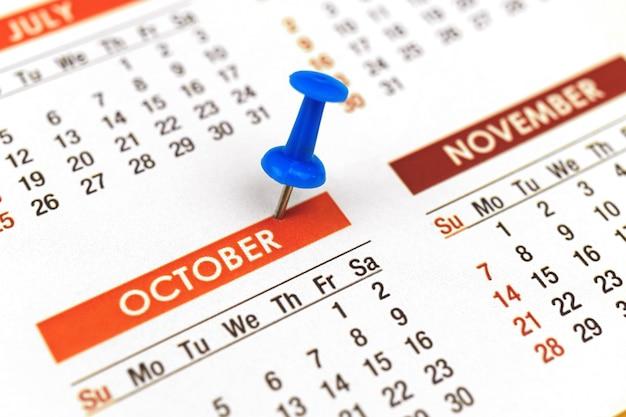 Calendario con puntina da disegno, primo piano del mese di ottobre, concetto di pianificatore, foto di messa a fuoco selettiva