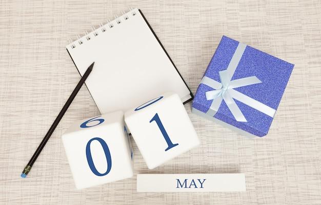 Calendario con testo blu e numeri alla moda per il 1 maggio e un regalo in una scatola.