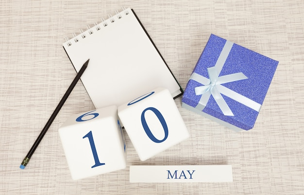 Calendario con testo blu e numeri alla moda per il 10 maggio e un regalo in una scatola.