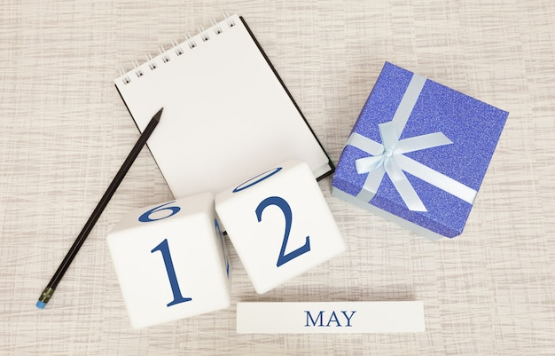 Calendario con testo blu e numeri alla moda per il 12 maggio e un regalo in una scatola.