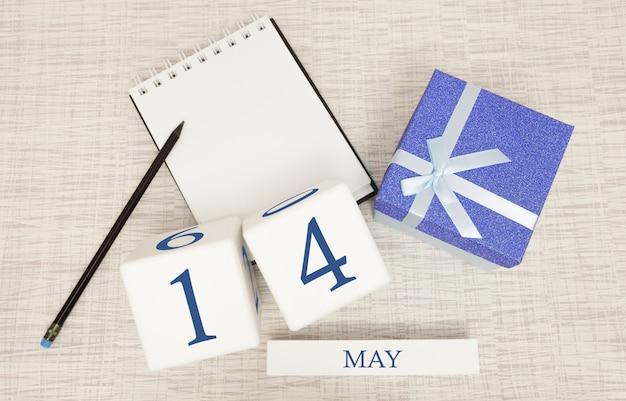 Calendario con testo blu e numeri alla moda per il 14 maggio e un regalo in una scatola.