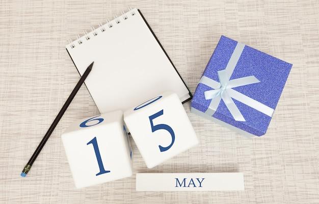Calendario con testo blu e numeri alla moda per il 15 maggio e un regalo in una scatola.