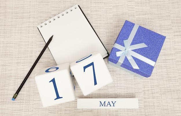 Calendario con testo blu e numeri alla moda per il 17 maggio e un regalo in una scatola.