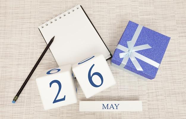 Calendario con testo blu e numeri alla moda per il 26 maggio e un regalo in una scatola.
