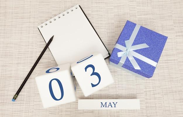 Calendario con testo blu e numeri alla moda per il 3 maggio e un regalo in una scatola.