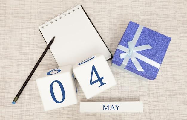 Calendario con testo blu e numeri alla moda per il 4 maggio e un regalo in una scatola.