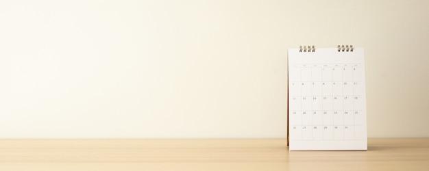 Calendario sulla tavola di legno con muro bianco