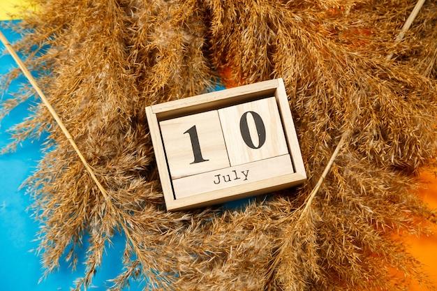 Calendario di cubi di legno con numeri e mesi. la scelta di un numero su un calendario in legno. luglio 1. data di luglio
