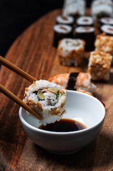 California roll sushi catturato dalle bacchette e introdotto in una ciotola di soia di salice con più pezzi di sushi in giro.