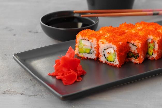 Il rotolo di sushi della california è servito sulla fine nera del piatto in ceramica
