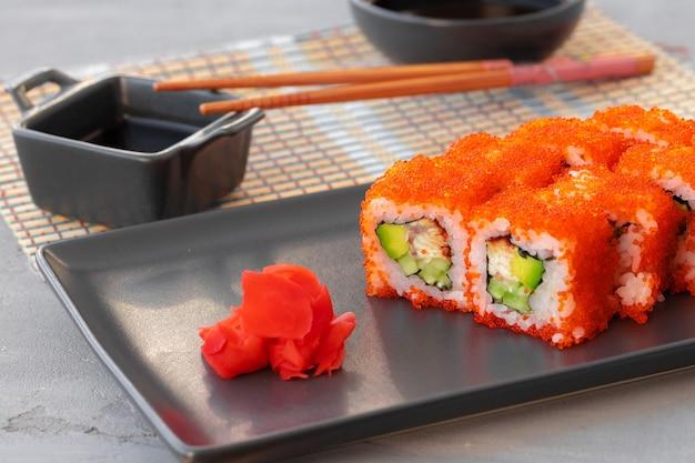 Il rotolo di sushi della california è servito sulla zolla di ceramica nera