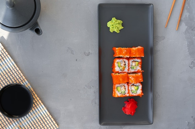 Il rotolo di sushi della california è servito sulla vista superiore del fondo grigio