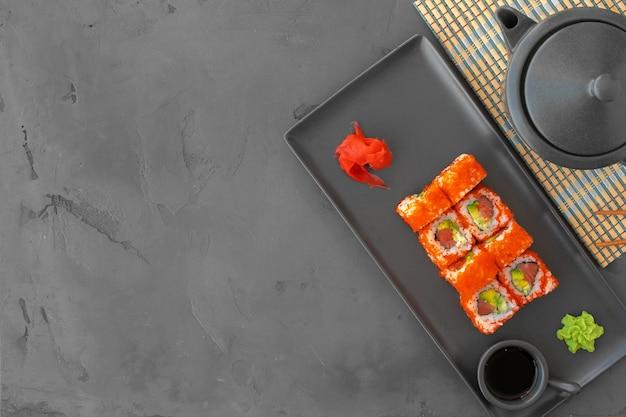 Rotolo di sushi della california servito su sfondo grigio