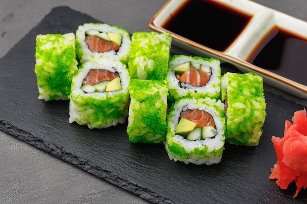 Rotolo di sushi della california con la fine verde del caviale su