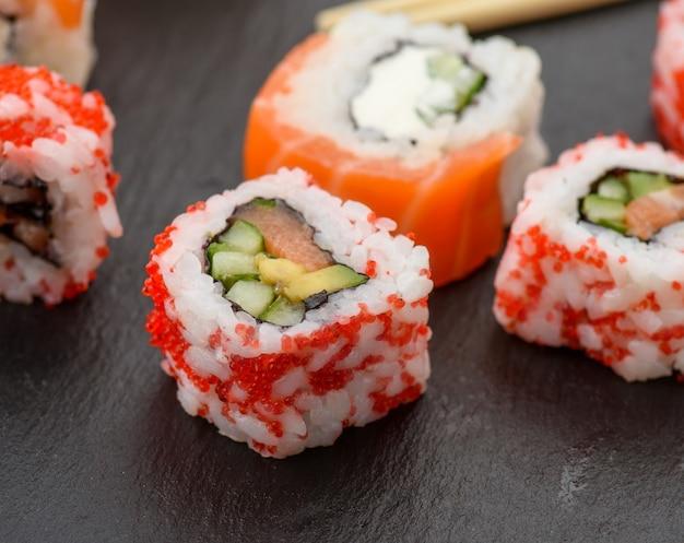 Sushi della california con il caviale rosso di tobiko e le fette di sushi di filadelfia sul bordo nero dell'ardesia, fine in su