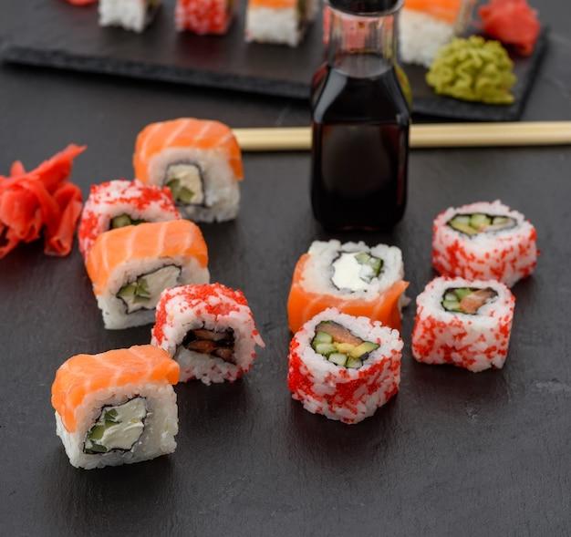 Sushi della california con il caviale rosso di tobiko e le fette di sushi di filadelfia sul bordo dell'ardesia nera, vista dall'alto